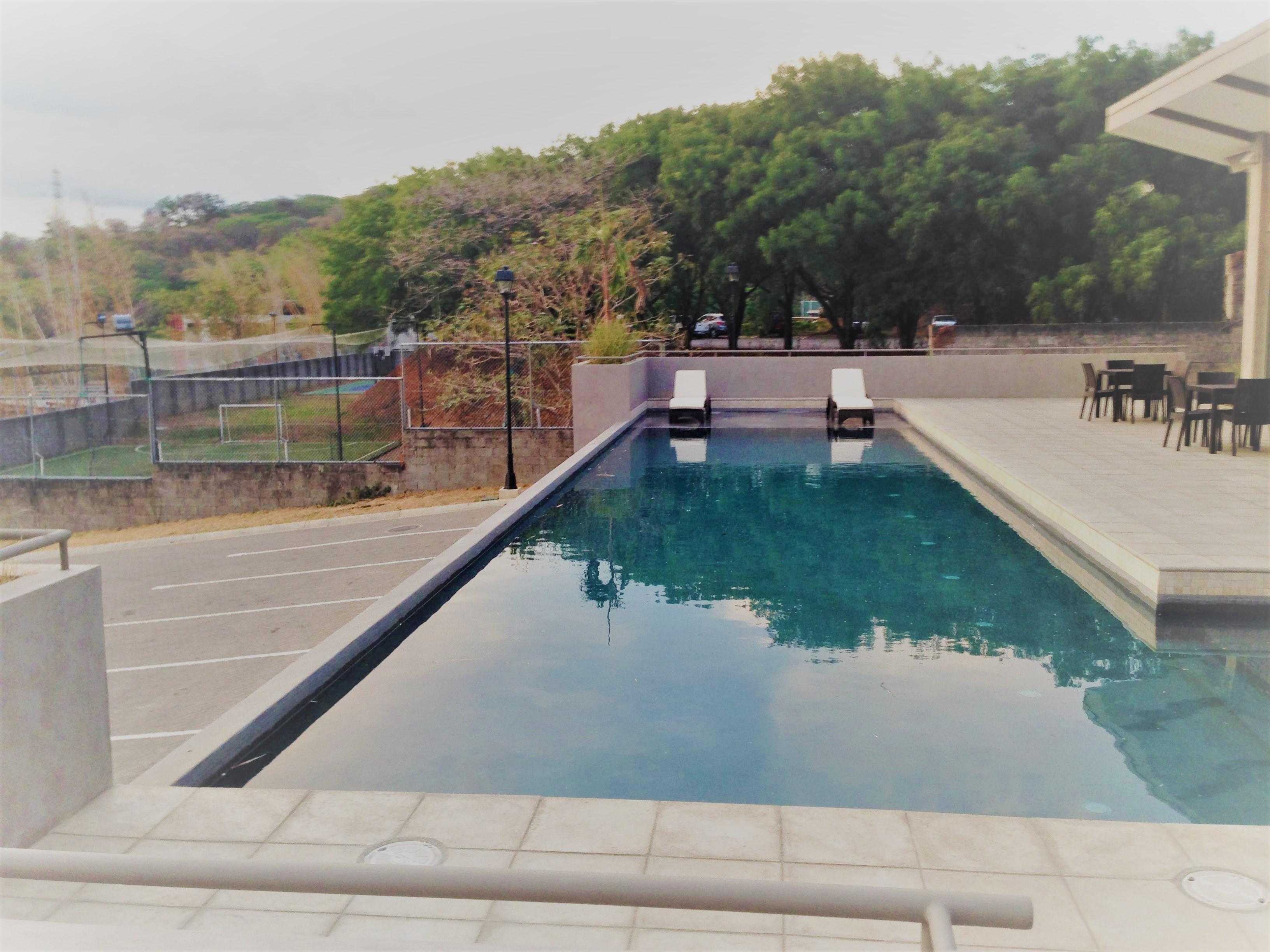 Moderna casa de 1 sola planta en condo con piscina for Construccion piscina temperada